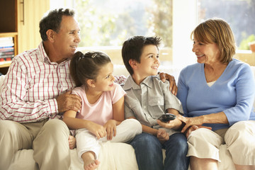 Hispanic Grandparents With Grandchildren Relaxing On Sofa At Home