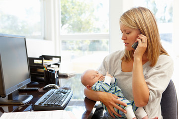 Mother working in home office with baby