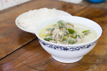 Thai green curry and Thai vermicelli on old table background