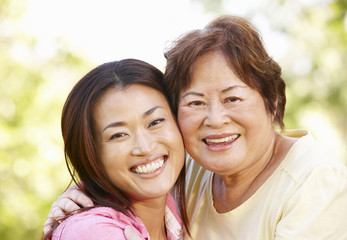 Asian mother and adult daughter head and shoulders outdoors