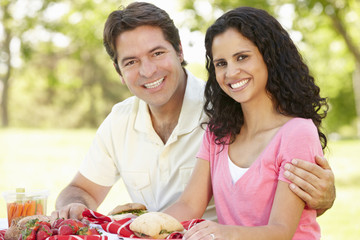 Young Hispanic Couple Enjoying Picnic In Park