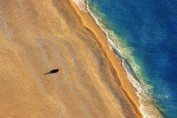 Lonely boat on a beach with aerial view.