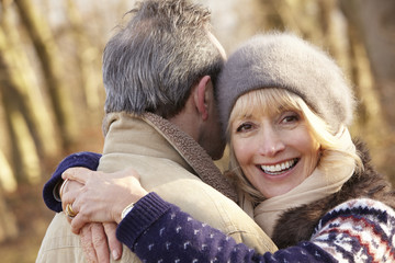 Senior couple hugging outdoors in winter