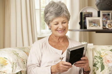 Happy Retired Senior Woman Sitting On Sofa At Home Looking At Photograph