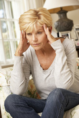 Unhappy Mature Woman Sitting On Sofa At Home