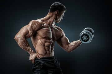 Power athletic man bodybuilder doing exercises with dumbbell