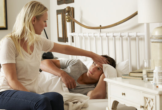 Sick Teenage Boy In Bed At Home Being Cared For By Mother