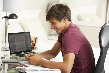 Teenage Boy Studying At Desk In Bedroom Using Mobile Phone