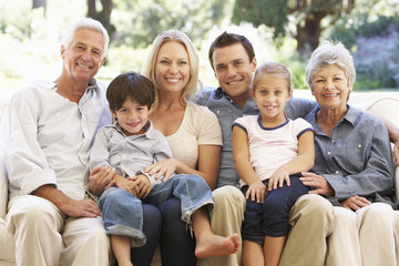Three Generation Family Sitting On Sofa At Home