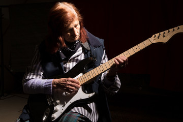 Funny elderly lady playing electric guitar.