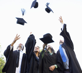 Group Of Students Attending Graduation Ceremony throwing Mortar Boards In The Air