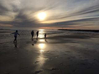 famila paseando al atardecer en la playa
