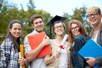 group of smiling students with diploma and folders