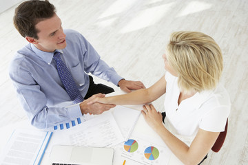 Overhead View Of Businesswoman And Businessman Working At Desk Together Shaking Hands
