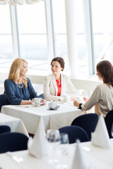 women drinking coffee and talking at restaurant