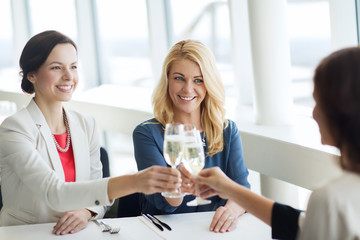 happy women drinking champagne at restaurant