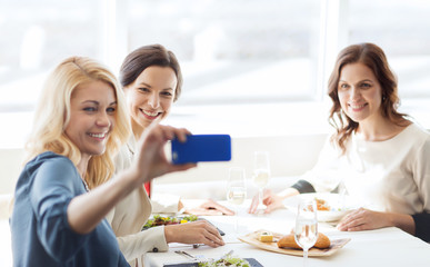 women with smartphone taking selfie at restaurant