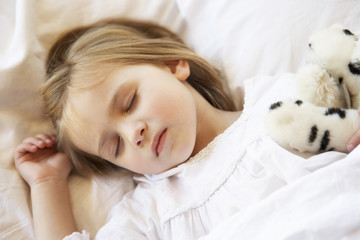 Young Girl Sleeping In Bed With Soft Toy