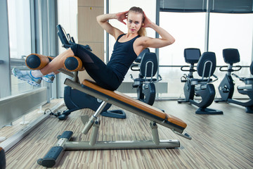 Beautiful sport woman doing press fitness exercise at gym