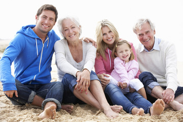 Multi Generation Family Sitting On Beach Together