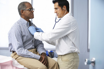 Doctor In Surgery Listening To Male Patient's Chest