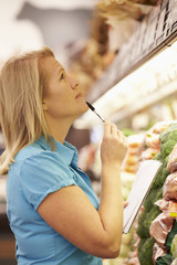 Woman Reading Shopping List In Supermarket
