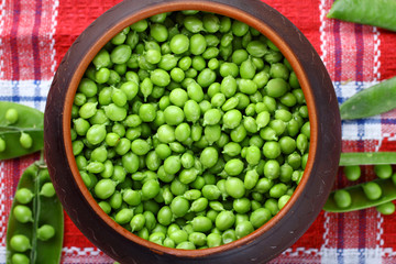 fresh green peas in a pot on a tablecloth