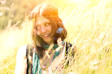 Hippie girl in the meadow in a photograph with vintage artifacts