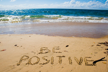 Be positive. Creative motivation concept written in the sand at the beach.
