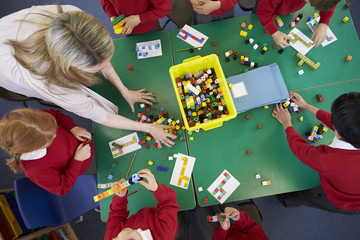 Overhead View Of Pupils And Teacher Working With Blocks