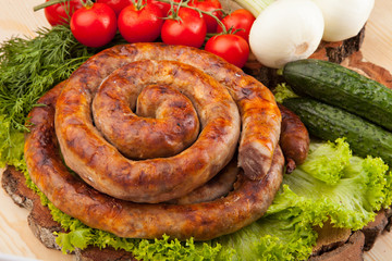 Smoked meat sausage salami with bright summer vegetables and bread on wooden background