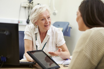 Consultant Showing Patient Test Results On Digital Tablet