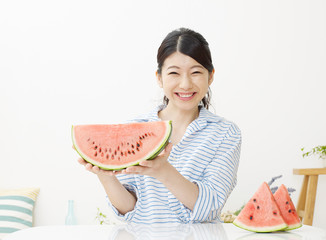屋で西瓜を食べる女性