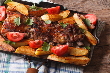 pork ribs, potatoes and tomatoes closeup. Horizontal top view