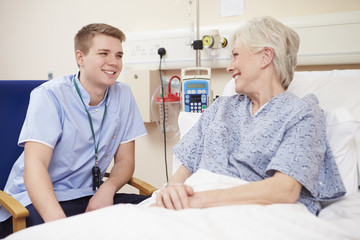 Male Nurse Sitting By Female Patient's Bed In Hospital