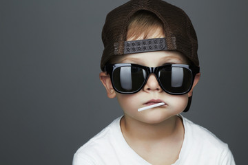 Funny Young Boy Eating A Lollipop.child in sunglasses