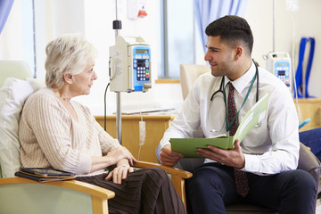 Woman Having Chemotherapy With Doctor Looking At Notes