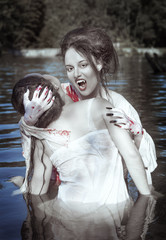 Beautiful vampire woman dressed white bloody shirt and her victi