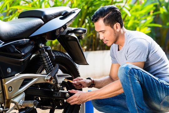 Asian man at motorcycle maintenance