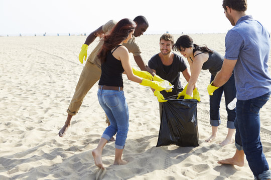 Group Of Volunteers Tidying Up Rubbish On Beach