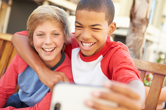 Two Boys Sitting On Bench In Mall Taking Selfie