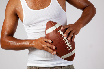 Young black man playing with American football