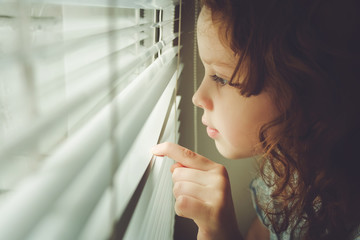 Little child looking out the window through the blinds. Backgrou