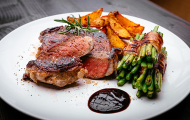 Juicy rib-eye steak with potatoe wedges and french beans