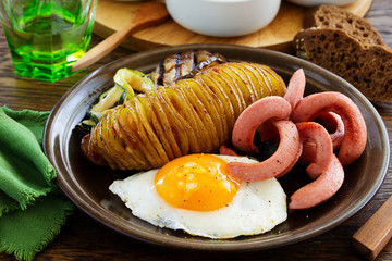 A hearty breakfast of baked potatoes (accordion), fried sausage, fried eggs