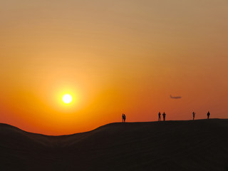 People make photo in the desert at the sunset