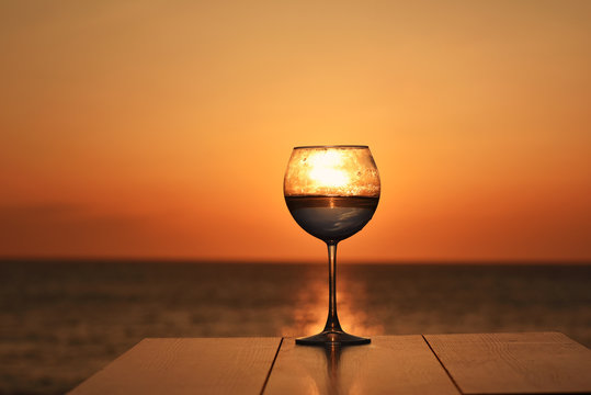 glass with wine at sunset on the table above the sea ocean
