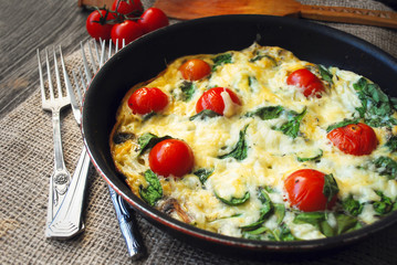 Frittata (italian omelet) with cherry tomatoes and spinach in pan on linen cloth. Angle view
