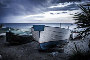 """Tipiche barche ligure """"gozzi"""" tirate in secca sulla spiaggia al tramonto"""