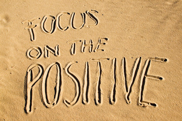 Focus on the positive. Creative motivation concept written in the sand at the beach.